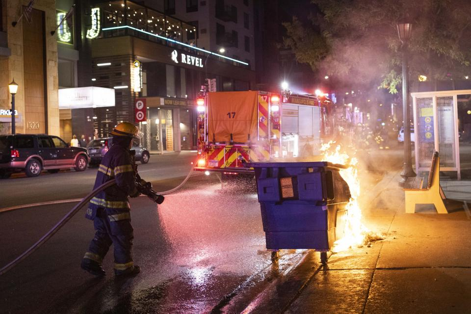A firefighter puts out a dumpster fire after protesters clash with police following a vigil that was held for Winston Boogie Smith Jr. early in on Saturday, June 5, 2021. Authorities said Friday that a man wanted on a weapons violation fired a gun before deputies fatally shot him in Minneapolis, a city on edge since George Floyd's death more than a year ago under an officer's knee and the more recent fatal police shooting of Daunte Wright in a nearby suburb. (AP Photo/Christian Monterrosa)