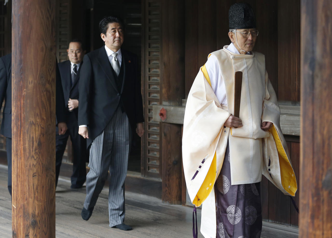 """Japanese Prime Minister Shinzo Abe, second from right, follows a Shinto priest to pay respect for the war dead at Yasukuni Shrine in Tokyo Thursday, Dec. 26, 2013. Abe visited Yasukuni war shrine in a move sure to infuriate China and South Korea. The visit to the shrine, which honors 2.5 million war dead including convicted class A war criminals, appears to be a departure from Abe's """"pragmatic"""" approach to foreign policy, in which he tried to avoid alienating neighboring countries. It was the first visit by a sitting prime minister since Junichiro Koizumi went to mark the end of World War II in 2006. (AP Photo/Shizuo Kambayashi)"""