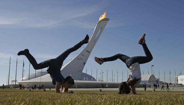 Young girls play on a warm day in the Olympic Plaza during the 2014 Winter Olympics, Wednesday, Feb. 12, 2014, in Sochi, Russia. (AP Photo/Darron Cummings)