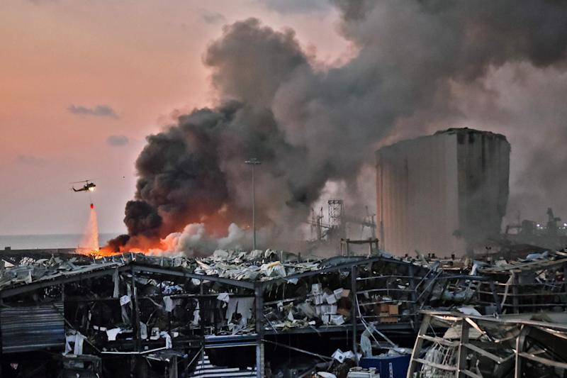 A helicopter puts out a fire at the scene of an explosion at the port of Lebanon's capital, Beirut, on Aug. 4.