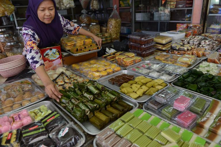 A vendor arranges a display of fresh local snacks at a market in Jakarta on November 28, 2014