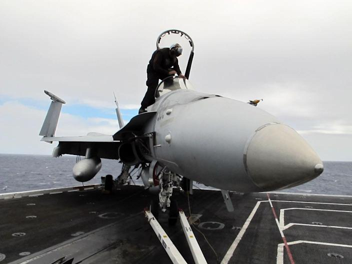 In this photo taken Wednesday, July 18, 2012, U.S. Navy Airman Dylan Blank of Strike Fighter squadron VFA-146 prepares a fighter jet aboard the USS Nimitz aircraft carrier. The U.S. Navy is using its Rim of the Pacific exercises to test whether aircraft and sea vessels run the same using fuels made up of biofuel blends rather than traditional petroleum. (AP Photo/Oskar Garcia)