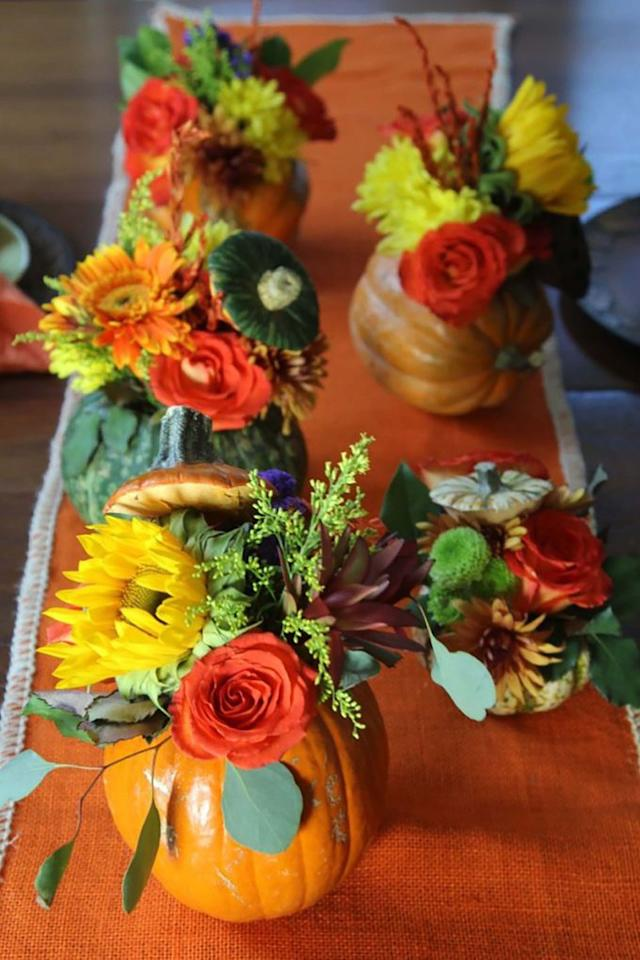 "<p>No need to buy pumpkin vases when you can use the real thing! Cut a hole in the top of the pumpkin and remove the seeds like you would when carving, then fill with your favorite fall flower.</p><p><strong>Get the tutorial at <a rel=""nofollow"" href=""https://www.delicioustable.com/thanksgiving-table-pumpkin-flower-centerpieces/"">Delicious Table</a>.</strong> </p>"