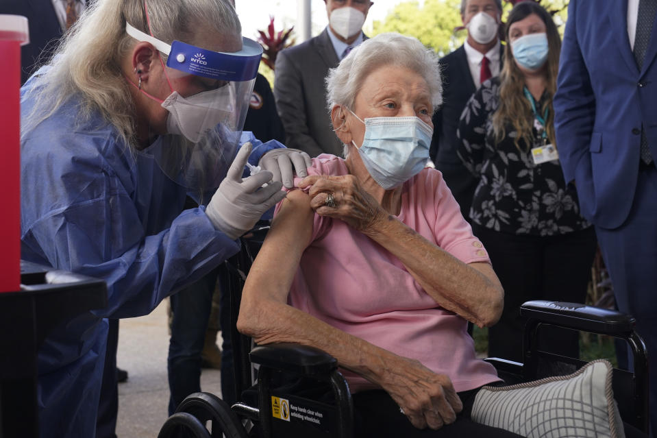 Nurse Christine Philips, left, administers the Pfizer vaccine to Vera Leip, 88, a resident of John Knox Village, Wednesday, Dec. 16, 2020, in Pompano Beach, Fla. Nursing home residents and health care workers in Florida began receiving the Pfizer vaccine this week. (AP Photo/Marta Lavandier)