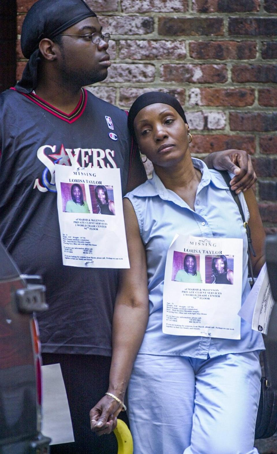 Two people wear posters of a missing woman as they seek information following the attack on the World Trade Centre (EPA)