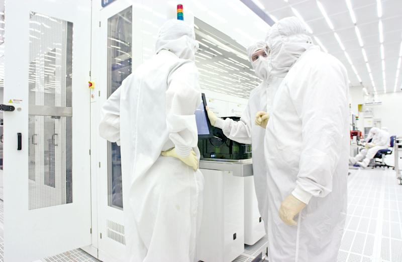 Three workers in head-to-toe white lab suits confer in a laboratory.
