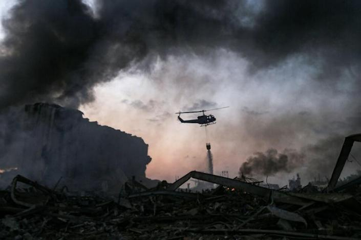 A helicopter puts out a fire at the scene of the explosions (AFP Photo/STR)