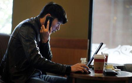 A man talks on the phone as he surfs the internet on his laptop at a local coffee shop in downtown Shanghai