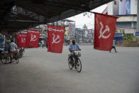 A man wearing mask as a precaution against COVID-19 pedals past flags of a Communist party trade union during a nation wide strike by various trade unions in Kochi, Kerala state, India, Thursday, Nov. 26, 2020. India has more than 9 million cases of coronavirus, second behind the United States. (AP Photo/R S Iyer)