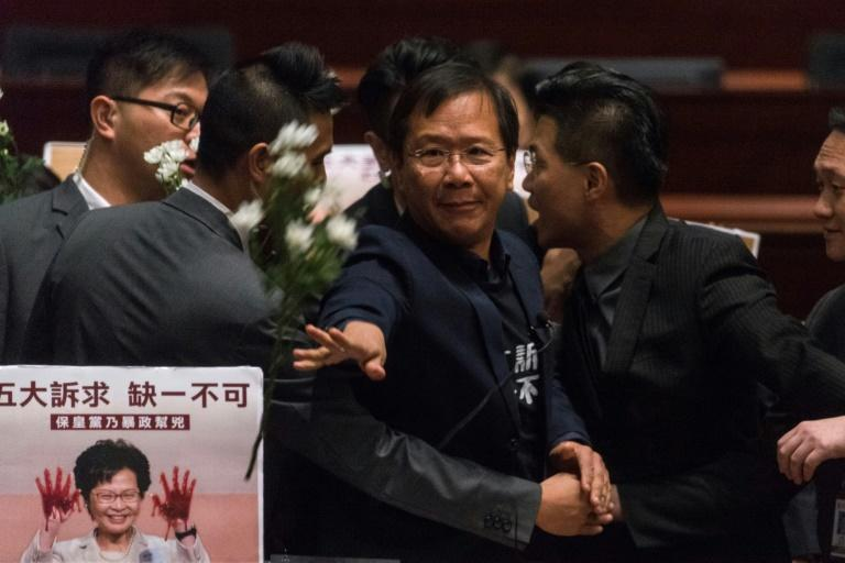 Hong Kong pro-democracy lawmaker Kwok Ka-ki (C) is removed by security from the Legislative Council after protesting as Chief Executive Carrie Lam held a Q&A session