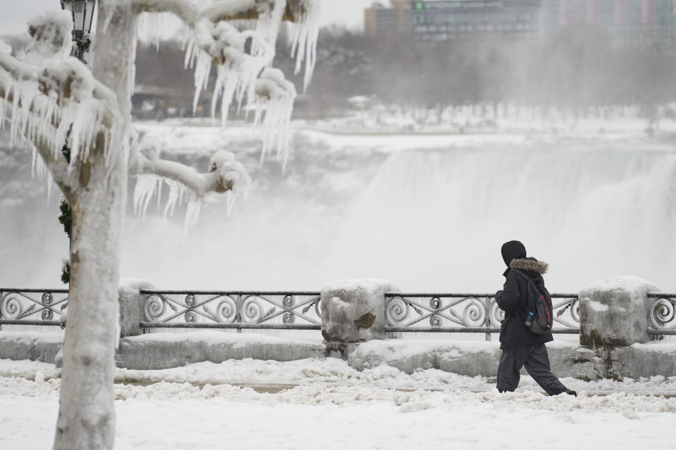 A man walks in the snow along the Niagara Parkway in Niagara Falls, Ontario, on January 27, 2021. (Photo by Geoff Robins / AFP) (Photo by GEOFF ROBINS/AFP via Getty Images)