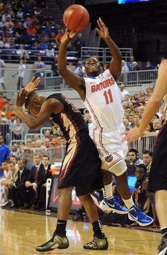 Florida's Erving Walker (11) tries to get rid of the ball before running down the shot clock with Florida State's Ian Miller (30) getting out of the way during the first half of an NCAA college basketball game in Gainesville, Fla., Thursday, Dec. 22, 2011. (AP Photo/ Phil Sandlin)