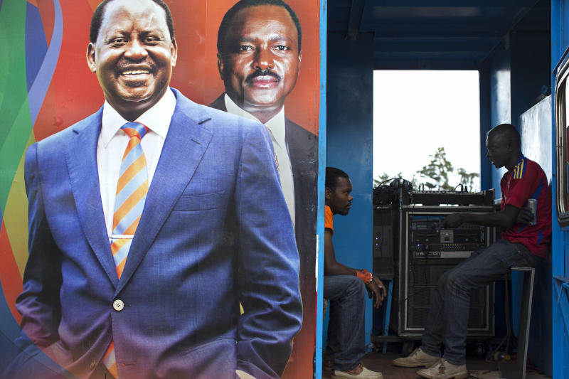 Large mural of Kenyan Prime Minister and Presidential candidate, Raila Odinga, and Current Vice President Kalonzo Musyoka, who will again run for vice president is seen as two campaign workers take a break after setting up the PA system for a ODM rally held in Kapkatet, Kenya, Friday, Feb. 22, 2013. Kenya will hold its national elections March 4, 2013. (AP Photo/Mackenzie Knowles-Coursin)
