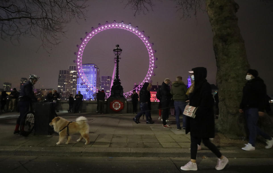 A group of people celebrate the start of the New Year as they look across from the embankment towards the London Eye ferris wheel by the River Thames in London, Friday, Jan. 1, 2021. The London Eye is one of the traditional sites for New Year's Eve firework display, but it has been cancelled due to the ongoing coronavirus pandemic and the restrictions in place to try and stop its spread.(AP Photo/Matt Dunham)