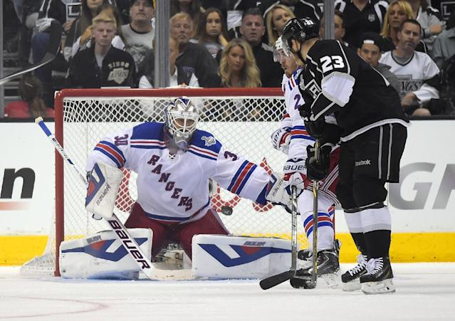 Los Angeles Kings right wing Dustin Brown, right, scores on New York Rangers goalie Henrik Lundqvist, left, of Sweden, as Rangers' Ryan McDonagh helps defend during the second overtime period in Game 2 of the NHL hockey Stanley Cup Finals, Saturday, June 7, 2014, in Los Angeles. The Kings won 5-4. (AP Photo/Mark J. Terrill)