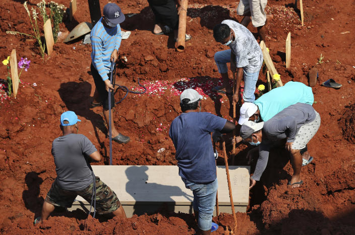 Workers lower a coffin into a grave at the special section of Jombang Public Cemetery reserved for those who died of COVID-19, in Tangerang, on the outskirts of Jakarta, Indonesia, Wednesday, Aug. 4, 2021. Indonesia surpassed 100,000 confirmed COVID-19 deaths on Wednesday, a grim milestone in a country struggling with its worst pandemic wave fueled by the delta variant, amid concerns the actual figure could be much higher. (AP Photo/Tatan Syuflana)