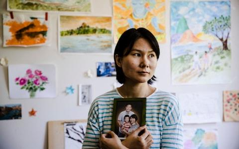 n this Wednesday, May 9, 2018 file photo, Hua Qu, the wife of detained Chinese-American Xiyue Wang, poses for a photograph with a portrait of her family in Princeton, N.J - Credit: AP