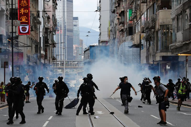 Riot police fire tear gas into the crowds to disperse anti-national security law protesters during a march at the anniversary of Hong Kong's handover to China from Britain in Hong Kong