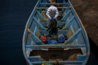 A police officer inspects a boat where 15 Malians were found dead adrift in the Atlantic on Thursday, Aug. 20, 2020 in Gran Canaria island, Spain. The 15 lifeless men were spotted inside a boat on Aug. 19 by a Spanish plane 80 nautical miles (148 kilometers, 92 miles) from the island of Gran Canaria. Police collected what was left behind as evidence: a wallet, a dozen cell phones, windbreakers and galoshes. (AP Photo/Emilio Morenatti)