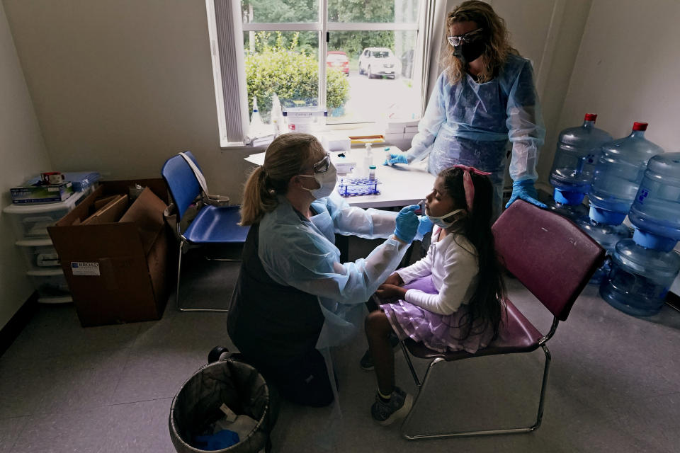 School nurse Denise Corrigan, left, tests a student for COVID-19 at the E.N. White School in Holyoke, Mass., on Wednesday, Aug. 4, 2021. Schools across the U.S. are about to start a new year amid a flood of federal money larger than they've ever seen before, an infusion of pandemic relief aid that is four times the amount the U.S. Department of Education sends to K-12 schools in a typical year. At right is testing program coordinator Nicole Mullett. (AP Photo/Charles Krupa)