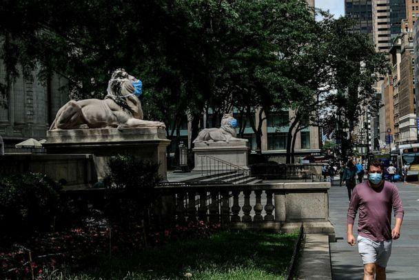 PHOTO: Patience and Fortitude, the marble lion statues at the entrance to the New York Public Library, are adorned with face masks on June 30, 2020, in New York. (Byron Smith/Getty Images)
