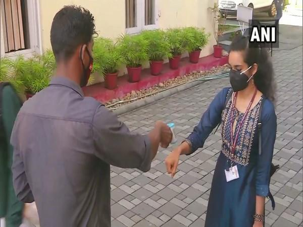 A student gets her temperature checked before entering the college campus. (Photo/ANI)