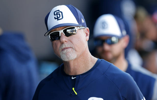 San Diego Padres bench coach Mark McGwire walks in the dugout during the fifth inning of a spring training baseball game against the Kansas City Royals, Friday, March 2, 2018, in Peoria, Ariz. (AP Photo/Charlie Neibergall)