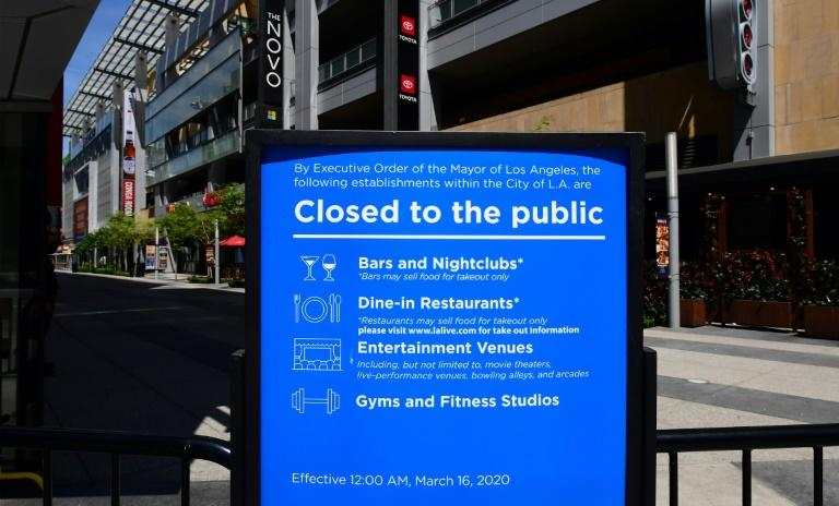 A sign in place since mid-March announces the temporary closures of restaurants, nightclubs gyms and entertainment venues at LA Live in Los Angeles