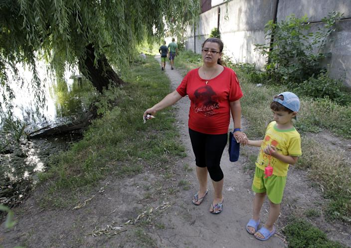 In this Wednesday, July 10, 2013 photo Natalia Pirogova, 36, a math teacher, standing together with her son, Sasha, shows the place where the body of a teenage girl was discovered two years ago in the town of Vradiyevka in southern Ukraine in a case that is still unresolved. Corruption, lawlessness and the impunity of government officials and their wealthy friends _ be it a national lawmaker, a businessman in an expensive car or a small town cop _ have increased significantly since the 2010 election of President Viktor Yanukovych, watchdogs say. (AP Photo/Sergei Chuzavkov)