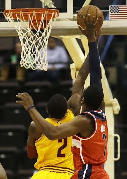 Washington Wizards point guard John Wall, right, blocks a shot by Cleveland Cavaliers point guard Kyrie Irving, left, in the first half of an NBA preseason basketball game on Wednesday, Oct. 23, 2013, in Cincinnati. (AP Photo/Al Behrman)