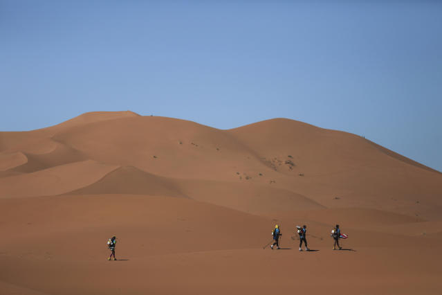 Competitors cross sand dunes as they take part in the final stage of the 33rd edition of Marathon des Sables during a sandstorm in the Sahara desert, near Merzouga, southern Morocco, Saturday, April 14, 2018. (AP Photo/Mosa'ab Elshamy)