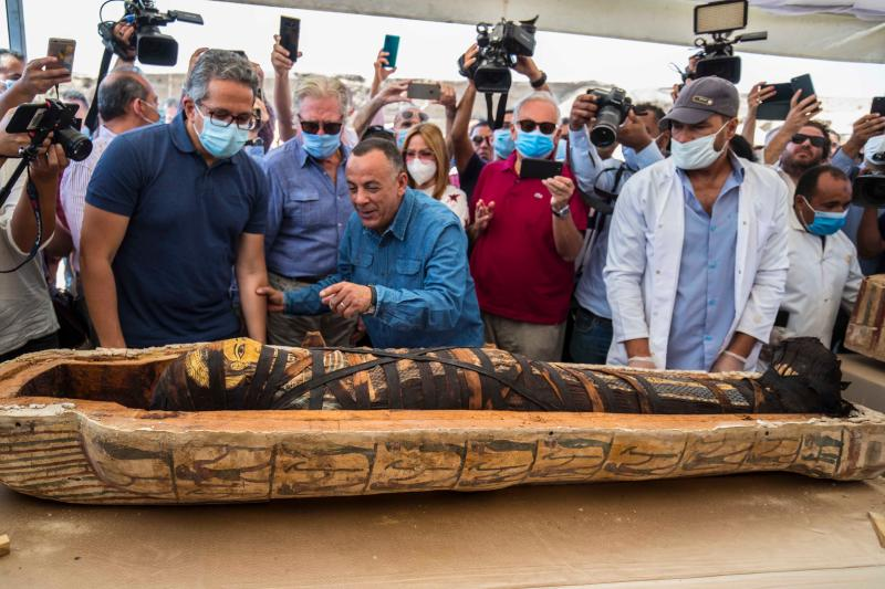 TOPSHOT - A picture taken on October 3, 2020 shows Egyptian Minister of Tourism and Antiquities Khaled Al-Anani (L), and Mustafa Waziri (R), Secretary General of the Supreme Council of Antiquities, unveil the mummy inside a sarcophagus excavated by the Egyptian archaeological mission working at the Saqqara necropolis, 30 kms south of the capital Cairo, which resulted in the discovery of a deep burial well with more than 59 human coffins closed for more than 2,500 years. - They were unearthed south of Cairo in the sprawling burial ground of Saqqara, the necropolis of the ancient Egyptian capital of Memphis, a UNESCO World Heritage site. Their exteriors are covered in intricate designs in vibrant colours as well as hieroglyphic pictorials. (Photo by Khaled DESOUKI / AFP) (Photo by KHALED DESOUKI/AFP via Getty Images)