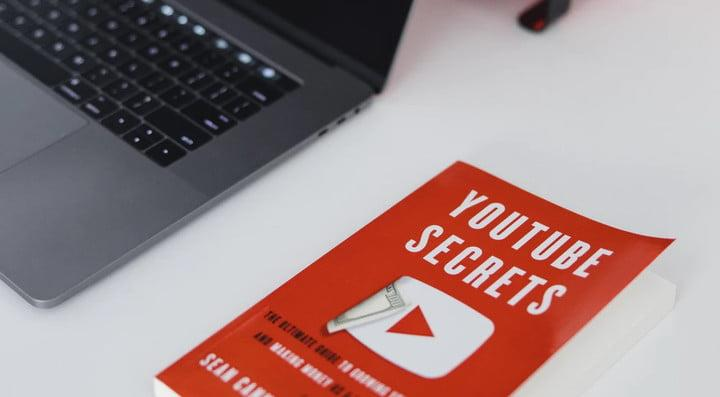 Un libro con secretos de Youtube junto a una laptop