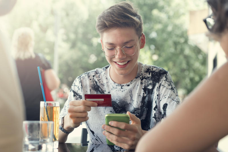 Teenager Boy and her friends Use credit card for shopping online in the cafeteria