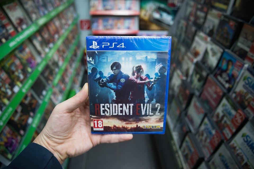 A person's hand holding the game 'Resident Evil 2.'