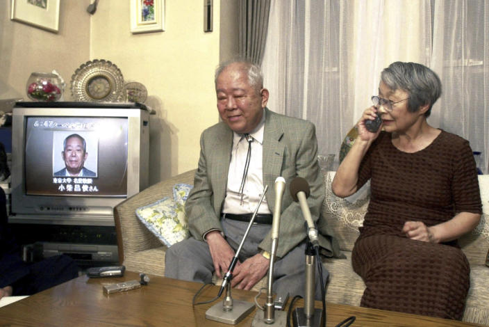 FILE - In this Oct. 8, 2002, Japanese physicist Masatoshi Koshiba sits with his wife Keiko Koshiba answering a congratulatory phone call as TV news reports his winning of the 2002 Nobel Prize in Physics at his home in Tokyo. Koshiba, a co-winner of the Nobel Prize for his pioneering researches into the make-up of the universe, died Thursday, Nov. 12, 2020, the University of Tokyo said. He was 94. (Kyodo News via AP, File)