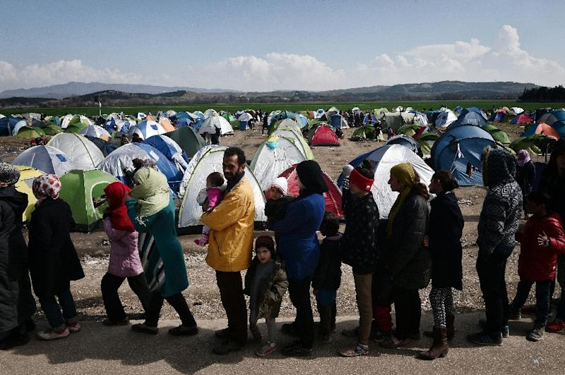 Refugees and migrants queue for food at the makeshift camp by the Greek-Macedonian borders near the Greek village of Idomeni, on March 2, 2016 (AFP Photo/Louisa Gouliamaki)