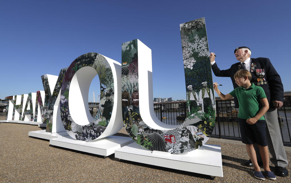 """RAF veteran Tom Weatherall, 84, and Alex Axford, 8, write a message on the side of the 8 foot tall and 52 foot wide 'Thank You' sign by artist Sarah Arnett on the bank of the River Thames in London, Friday, Aug. 3, 2018. The Royal British Legion has launched a movement to say """"Thank You"""" to all who served during the First World War with 100 days to go until Nov. 11. (AP Photo/Kirsty Wigglesworth)"""