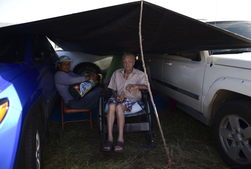 In this Friday, Jan. 10 photo, residents from the Indios neighborhood of Guayanilla, Puerto Rico, Milagros Figueroa and Ruben Fantausi, sit under a tarp between vehicles parked on a private hay farm where locals affected by earthquakes have set up shelter amid aftershocks in Guayanilla, Puerto Rico. A 6.4 magnitude quake that toppled or damaged hundreds of homes in southwestern Puerto Rico is raising concerns about where displaced families will live, while the island still struggles to rebuild from Hurricane Maria two years ago. (AP Photo/Carlos Giusti)