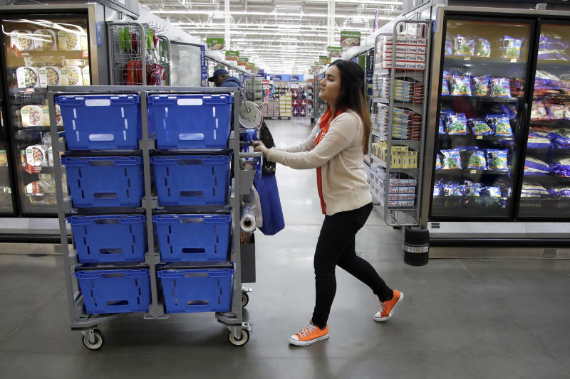 In this Thursday, Nov. 9, 2017, photo, Laila Ummelaila, a personal shopper at the Walmart store in Old Bridge, N.J., pushes a cart with bins as she shops for online shoppers. On Thursday, Jan. 11, 2018, Walmart announced it is boosting its starting salary for U.S. workers to $11 an hour, giving a one-time $1,000 cash bonus to eligible employees and expanding its maternity and parental leave benefits. (AP Photo/Julio Cortez)