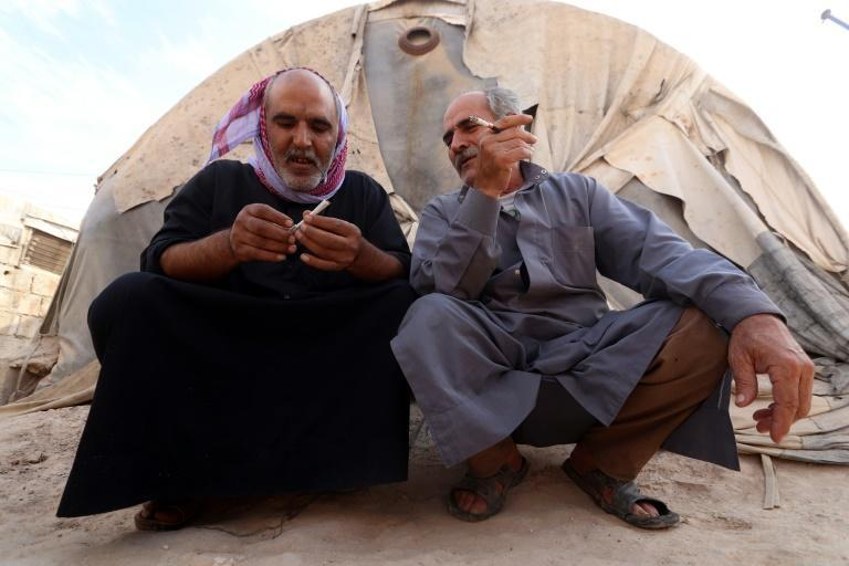 Displaced Syrian men in an overcrowded camp for the displaced near the village of Qah, near the border with Turkey