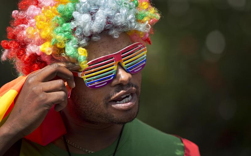 """A protester wears a rainbow-colored wig and glasses as Kenyan gays and lesbians and others supporting their cause stage a rare protest, against Uganda's increasingly tough stance against homosexuality and in solidarity with their counterparts there, outside the Uganda High Commission in Nairobi, Kenya Monday, Feb. 10, 2014. Homosexuality has been criminalized in Uganda where lawmakers have recently passed a new bill, which appears to have wide support among Ugandans, that prescribes life imprisonment for """"aggravated"""" homosexual acts. (AP Photo/Ben Curtis)"""