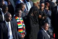 Zimbabwean President Emmerson Mnangagwa stands next to Grace Mugabe, after receiving the body of her husband, former Zimbabwean President Robert Mugabe in Harare