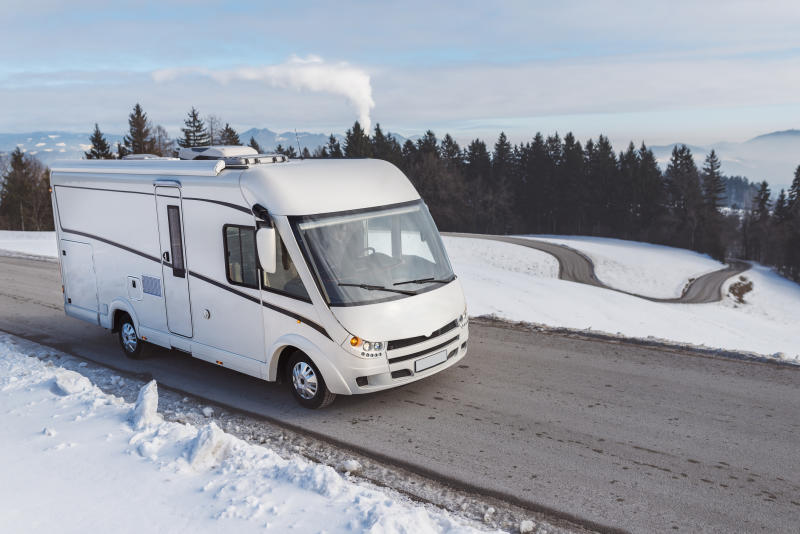 A motor home driving on a winding road with trees and a snowy landscape in the background