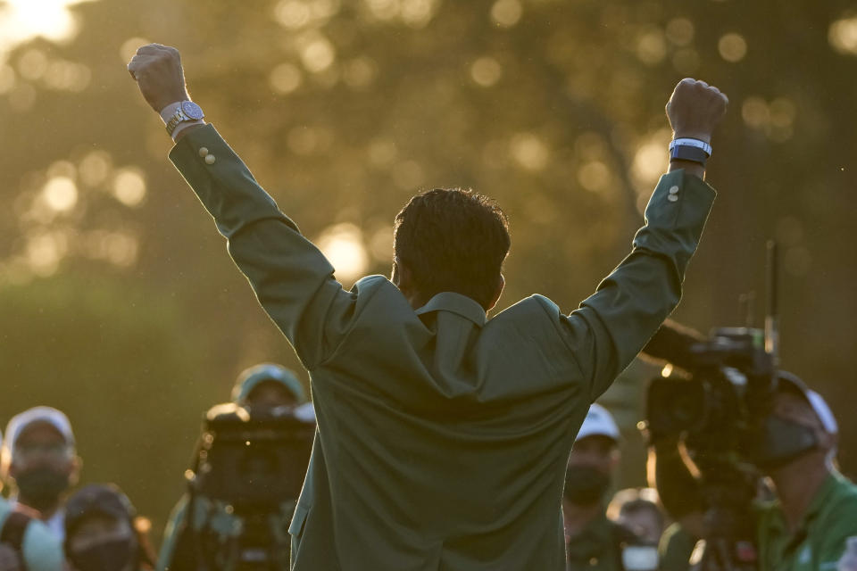 Hideki Matsuyama, of Japan, puts on the champion's green jacket after winning the Masters golf tournament on Sunday, April 11, 2021, in Augusta, Ga. (AP Photo/Charlie Riedel)