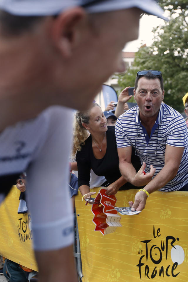 A man makes a gesture of injecting himself as he he shows his disapproval of Britain's Chris Froome, left, prior to the fifteenth stage of the Tour de France cycling race over 181.5 kilometers (112.8 miles) with start in Millau and finish in Carcassonne, France, France, Sunday July 22, 2018. Froome, under suspicion of doping because of high salbutamol levels, was cleared of doping by the International Cycling Union in a decision that will allow him to pursue a record-tying fifth Tour de France. (AP Photo/Christophe Ena )
