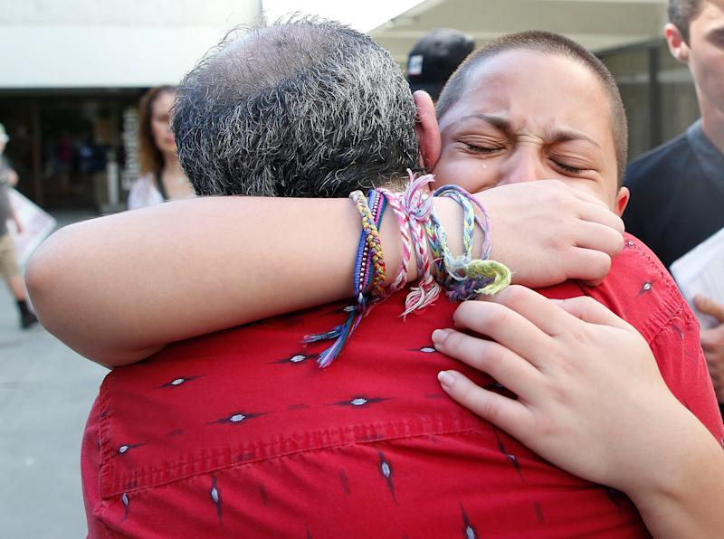 Marjory Stoneman Douglas High School student Emma González hugs her father Jose after speaking at a rally for gun control at the Broward County Federal Courthouse in Fort Lauderdale, Florida on Feb. 17, 2018.