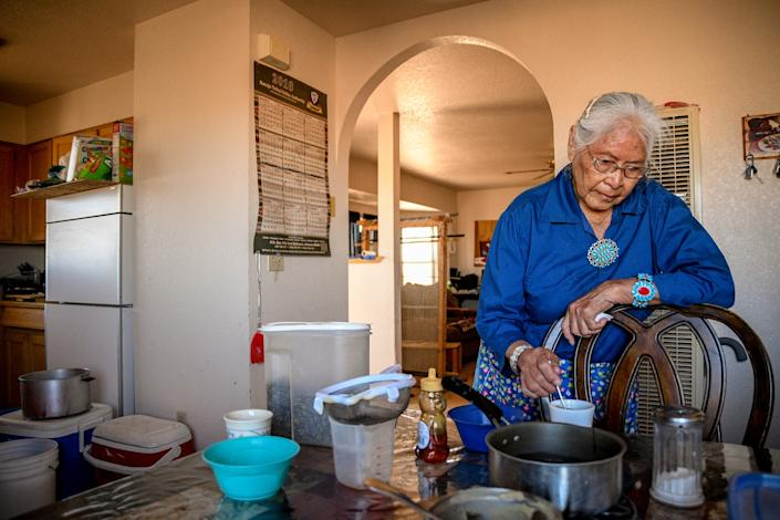 Cecilia Joe stirs her tea at her home near Tuba City. (Photograph by Mary F. Calvert)