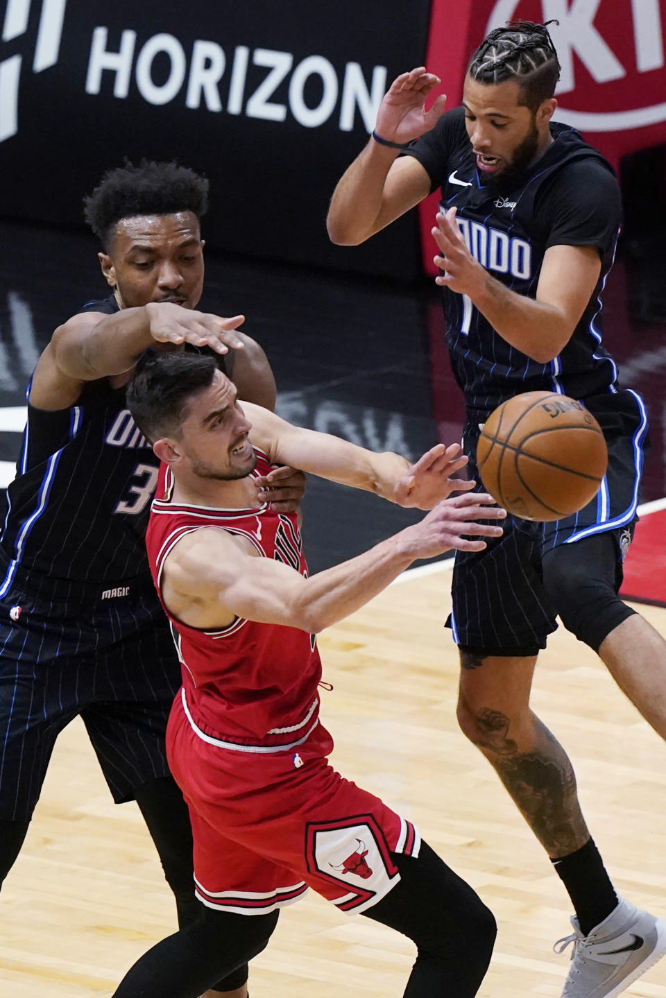 Chicago Bulls guard Tomas Satoransky, center, passes the ball as Orlando Magic center Wendell Carter Jr., left, and guard Michael Carter-Williams defend during the first half of an NBA basketball game in Chicago, Wednesday, April 14, 2021. (AP Photo/Nam Y. Huh)