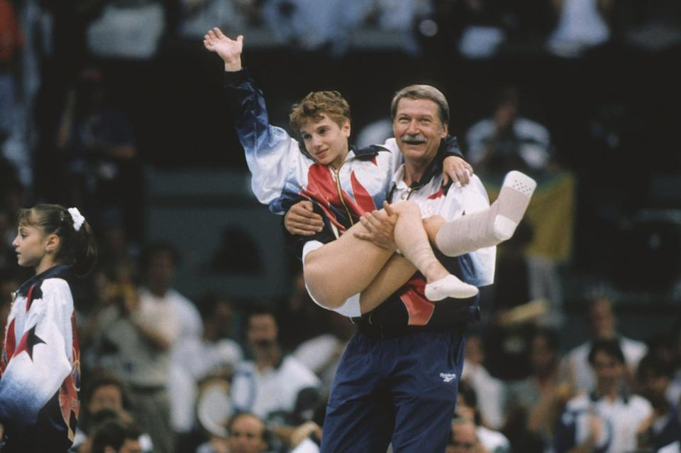 ATLANTA - JULY 23:  Kerri Strug of the United States is carried by coach Bela Karolyi during the team competition of the Women's Gymnastics event of the 1996 Summer Olympic Games held on July 23, 1996 in the Georgia Dome in Atlanta, Georgia.  Strug was part of the gold medal winning USA Women's team, nicknamed the Magnificent Seven.  (Photo by David Madison/Getty Images)
